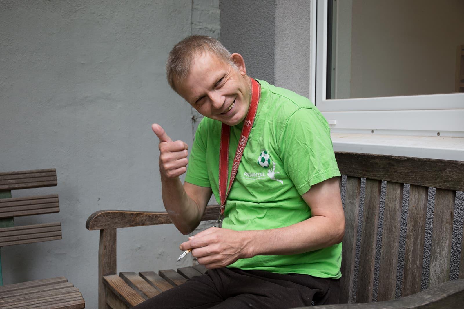 Ein Klient des Matthias-Claudius-Haus in Wersten lacht in die Kamera.