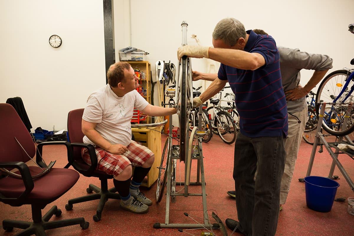 Mehrere Klienten reparieren ein Fahrrad in der Klienten-Fahrradwerkstatt