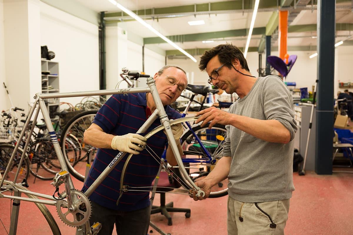 Ein Klient repariert gemeinsam mit einem Betreuer ein Fahrrad in der Fahrradwerkstatt
