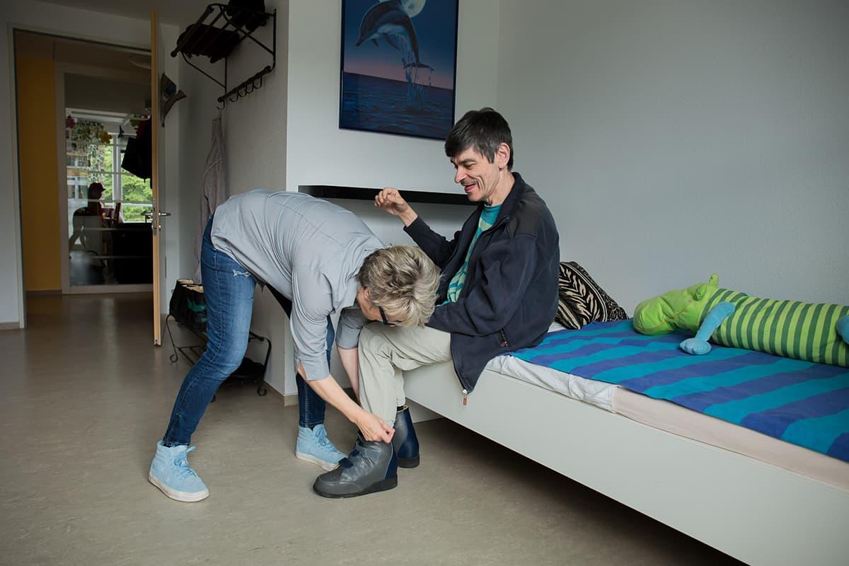 Eine Betreuerin hilft einem Klienten beim Anziehen im Matthias-Claudius-Haus in Wersten