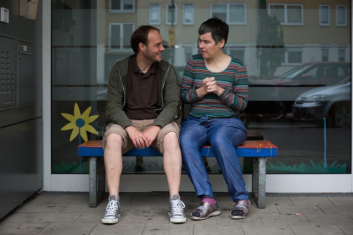 Zwei Personen sitzen vertieft in ein Gespräch vor dem Matthias-Claudius-Haus in Wersten