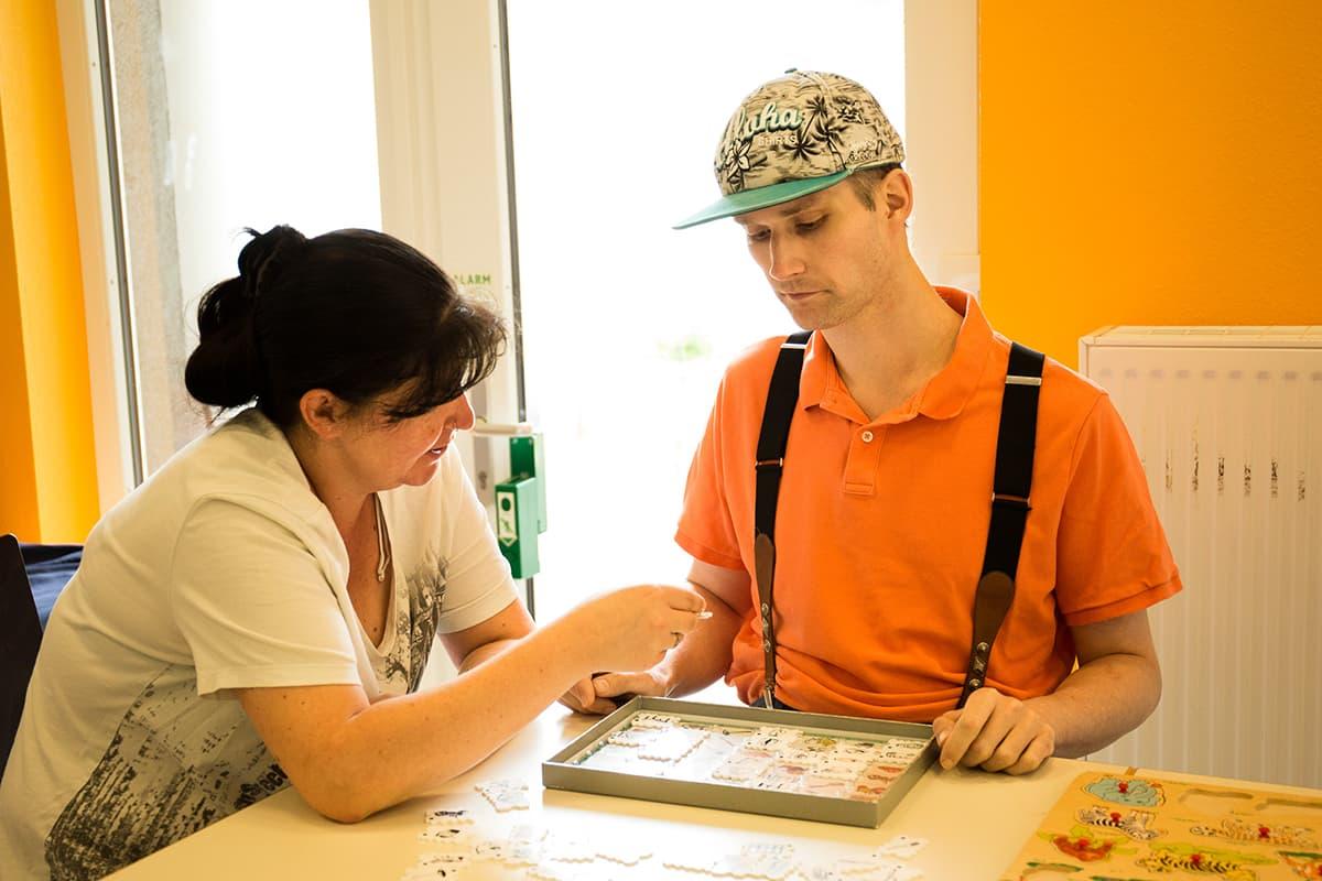 Eine Betreuerin und ein Klient spielen gemeinsam ein Puzzle im Matthias-Claudius-Haus in Wersten