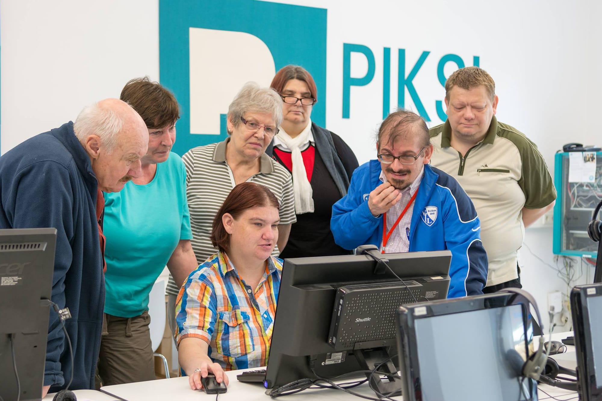 Eine Personengruppe steht um eine Frau am Computer herum.