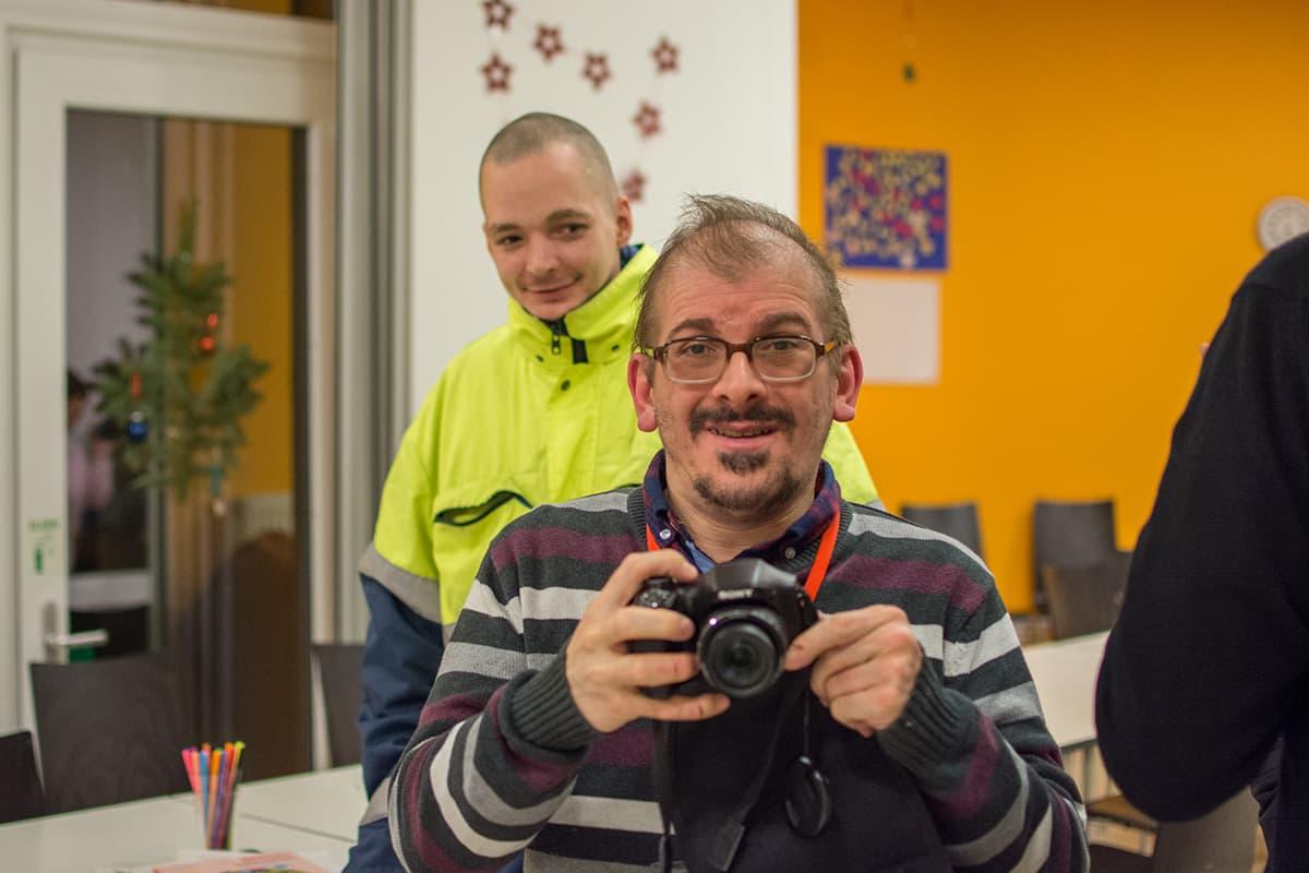 Ein Mann fotografiert während im eine anderer Mann über die Schulter schaut.